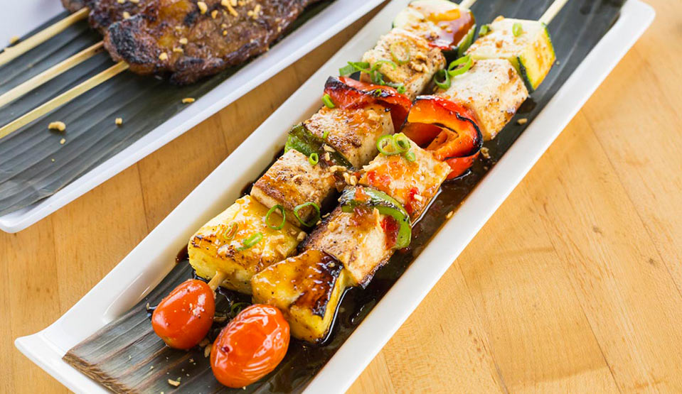 Barbecued meats and veggies skewered and plated.
