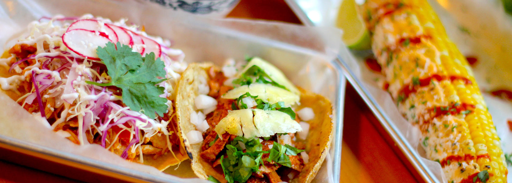 Brightly dressed tacos and buttered street corn on metal trays.