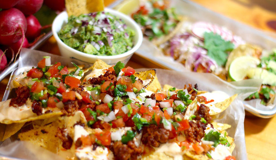 Nacho chips loaded with barbecued meats, salsa with side of guacamole.