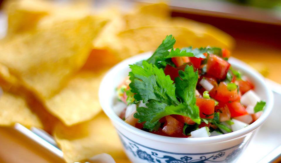 Fresh chopped salsa with chips in background.