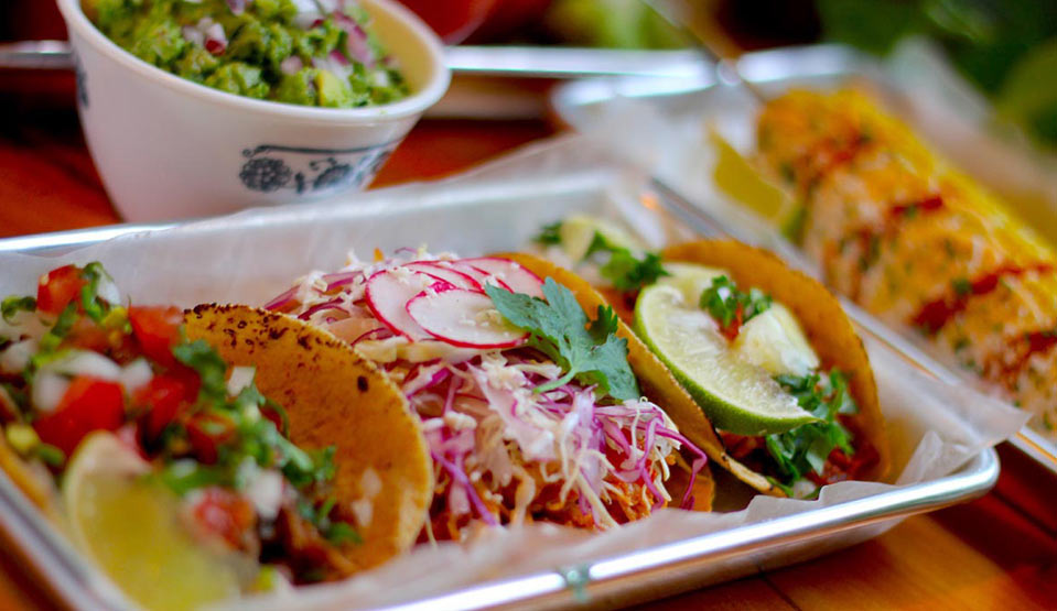 Set of three different tacos with guacamole and buttered street corn.