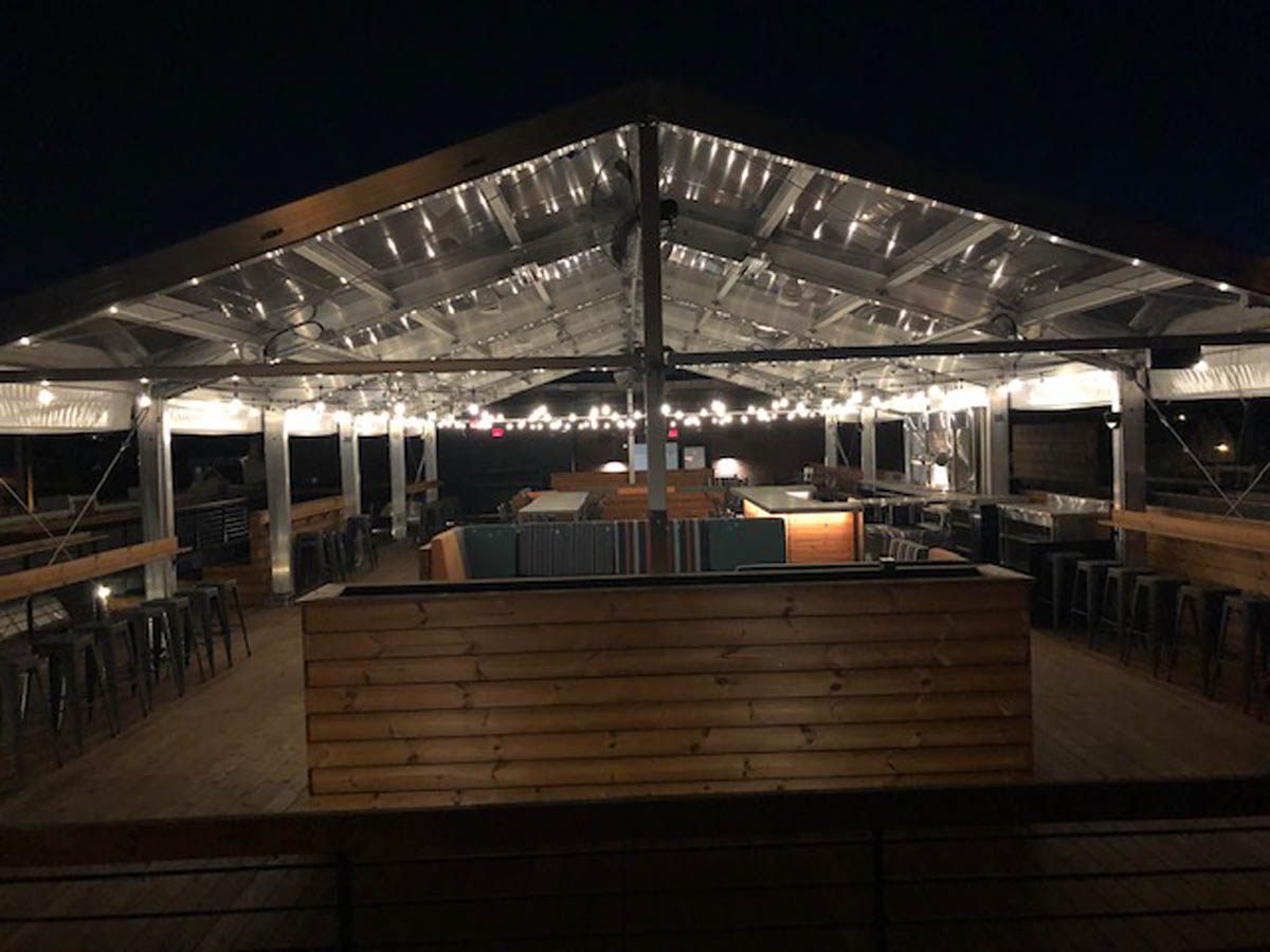 Image of the outdoor patio at Budd Dairy Food Hall at night with patio lights on.