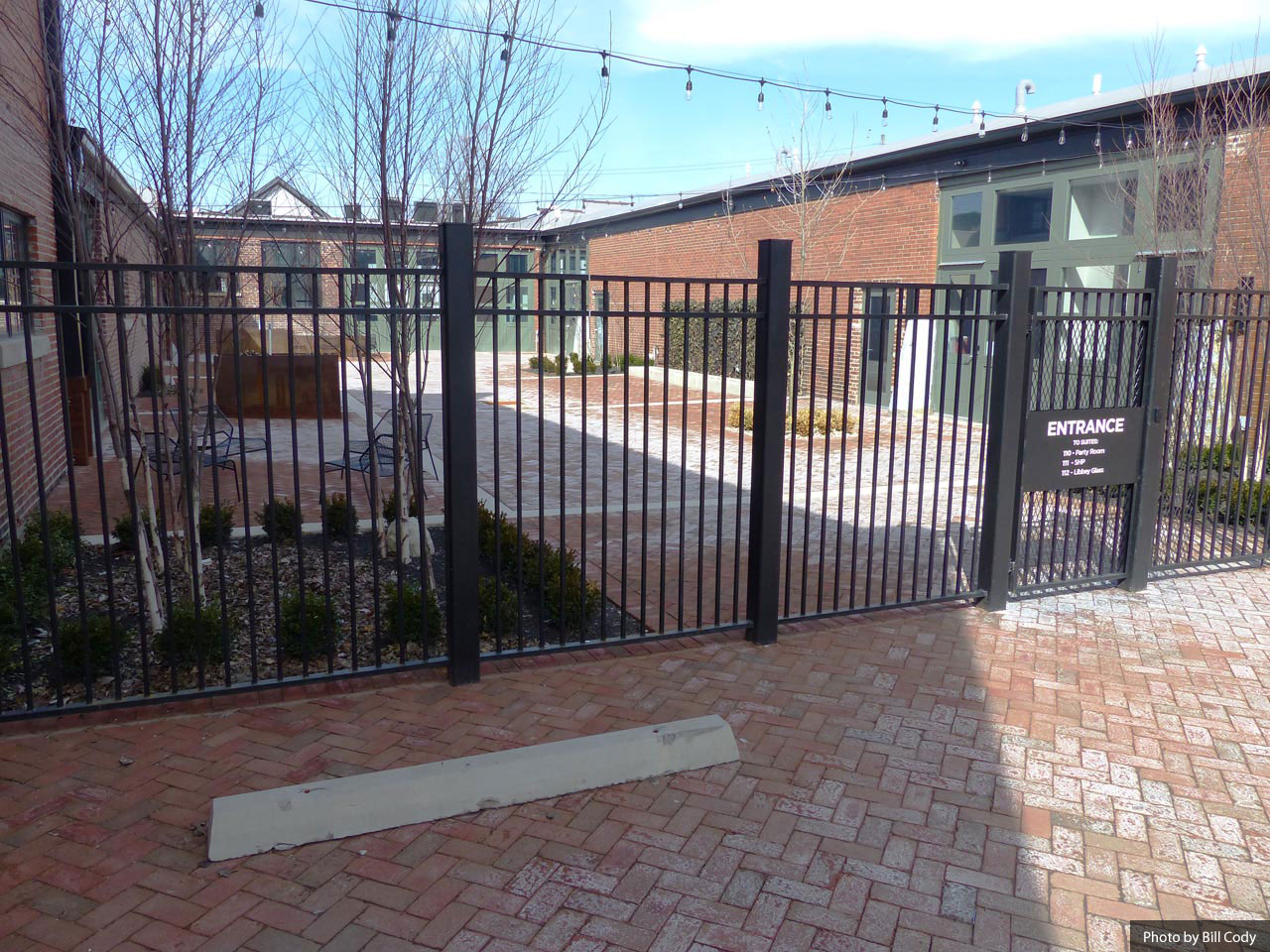 Budd Dairy exterior beer garden area with dark gray metal fencing.