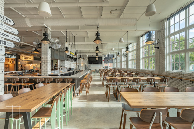 Open air seating inside space with large windows inside Budd Dairy Food Hall, Columbus Ohio.