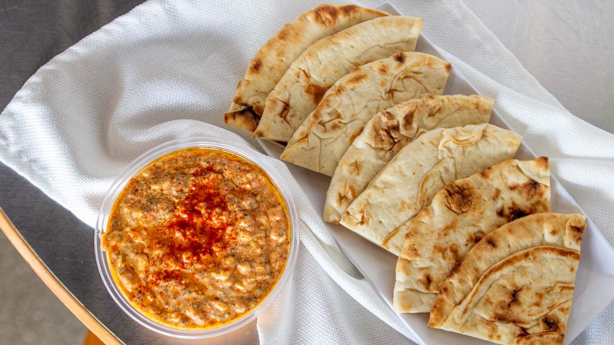 Row of pita breads with spicy feta dip in bowl
