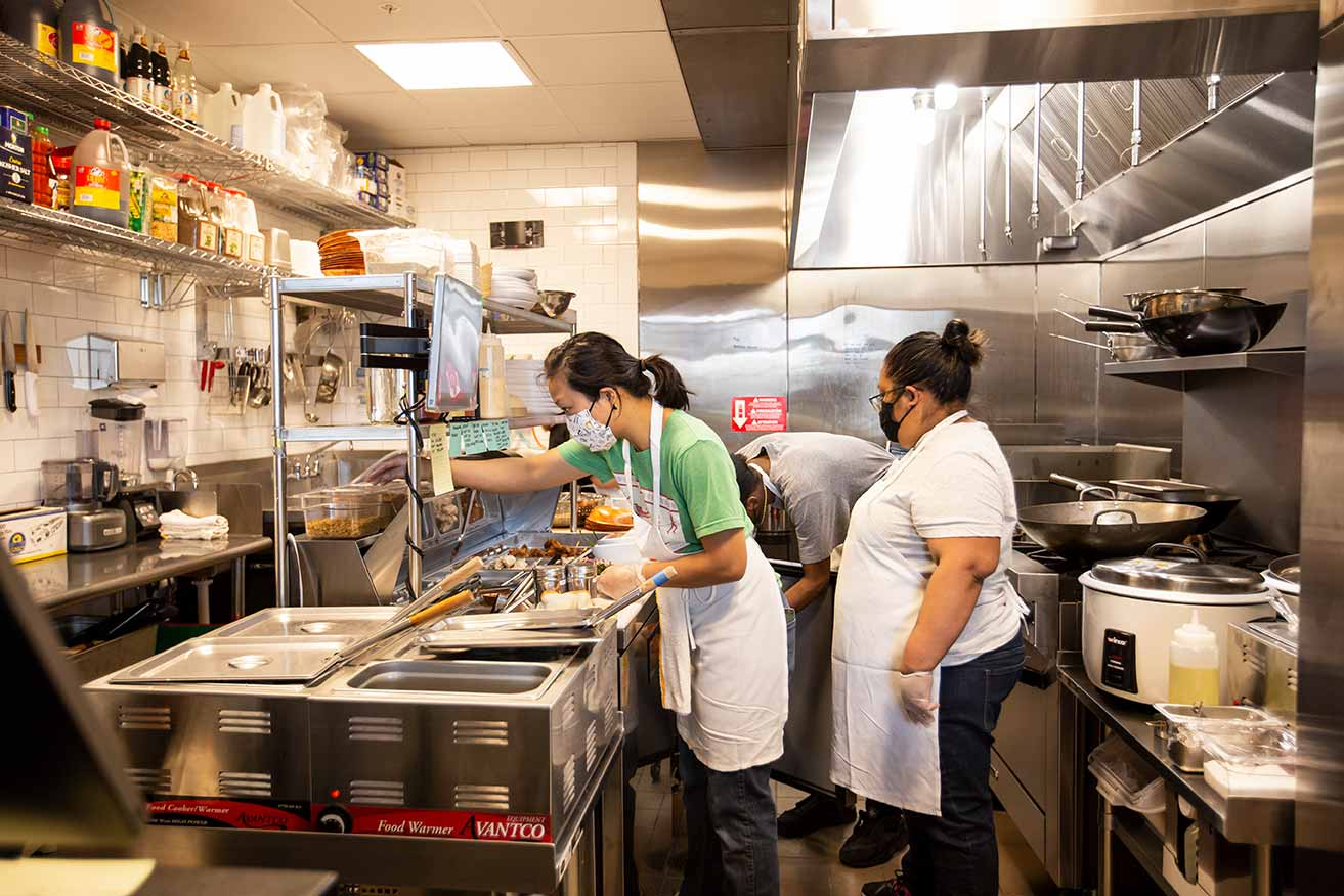 Women working on food order in bright, stainless steel kitchen.,