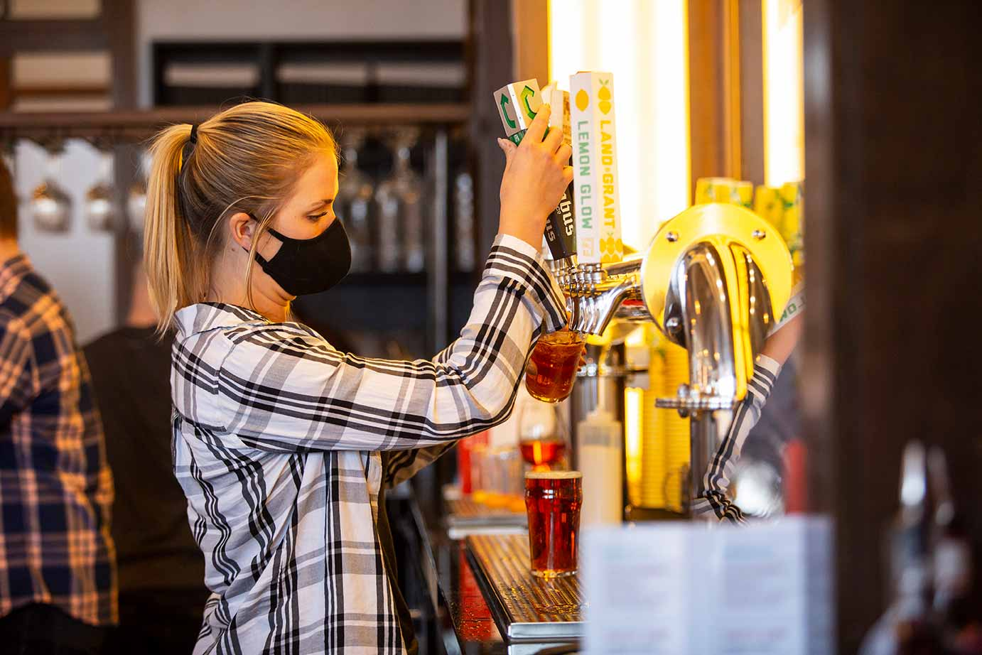 Young woman drawing down a draft beer behind a bar.