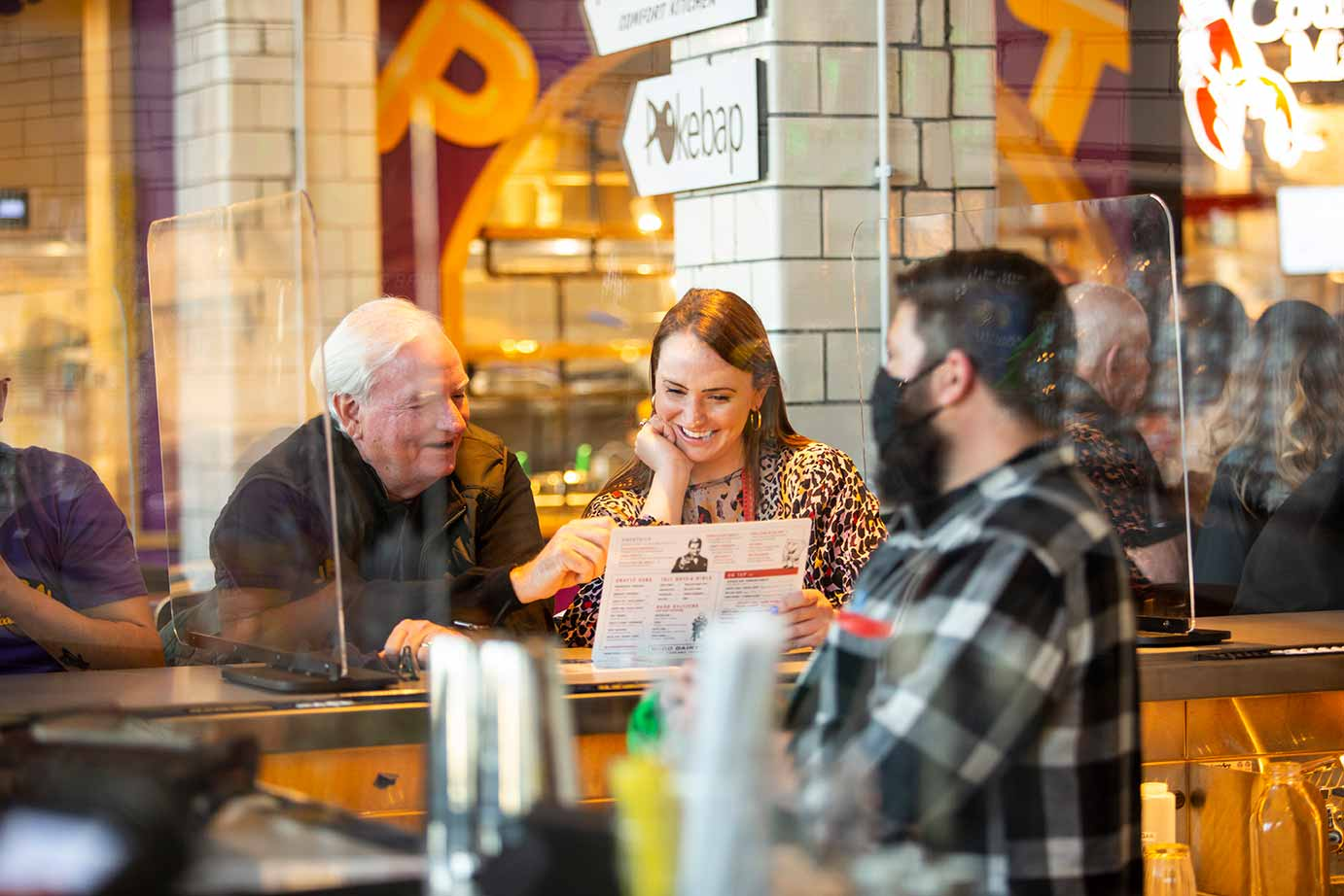 Older man with smiling young woman reviewing a menu while seated at a bar.