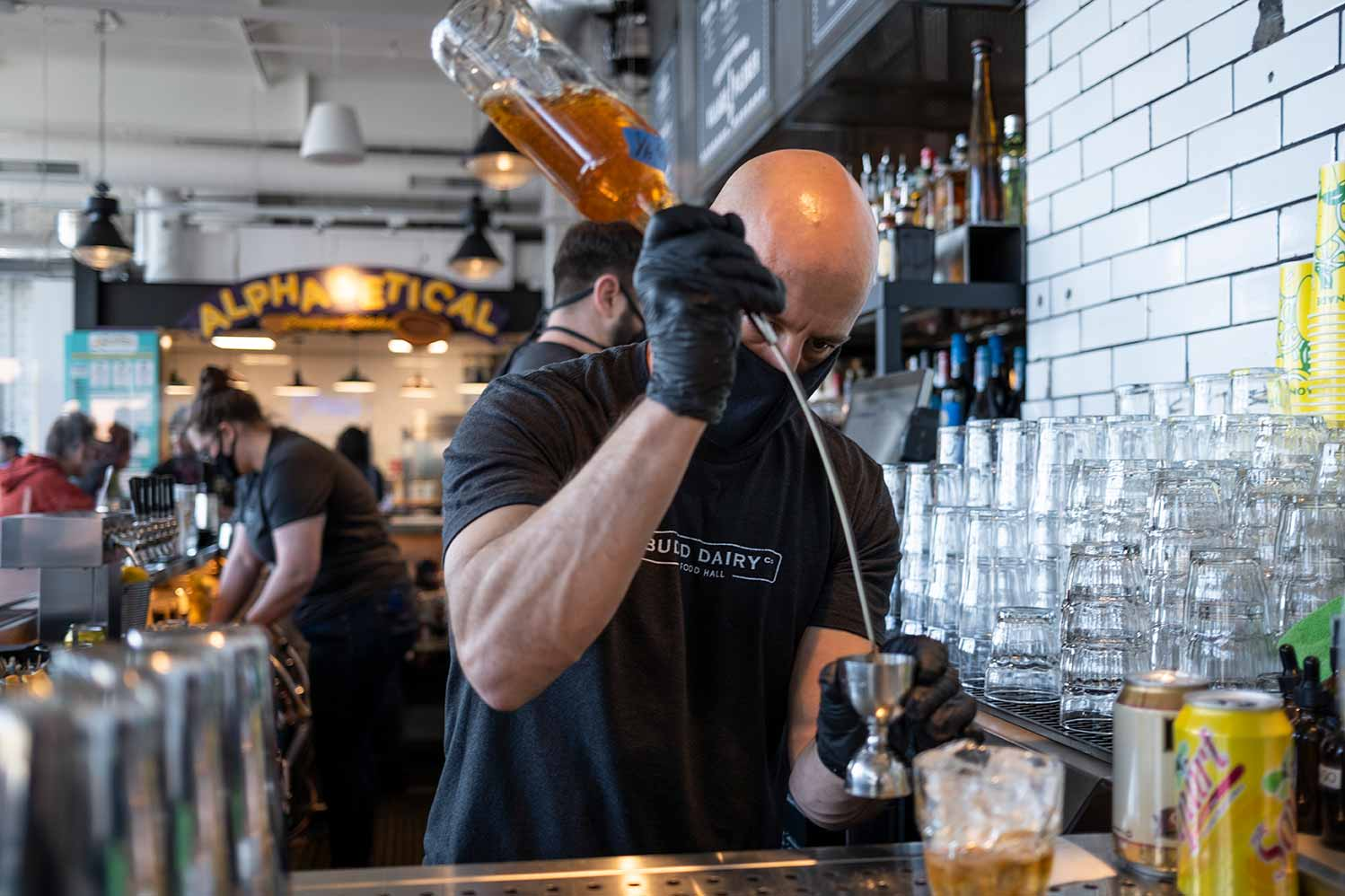 Bartender with one arm raised pouring liquor into glass below.