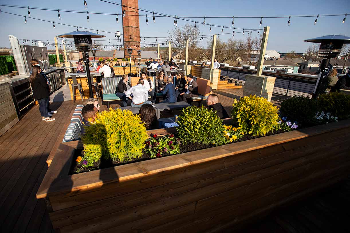 Groups of people seated on the sunny rooftop of Budd Dairy Food Hall.