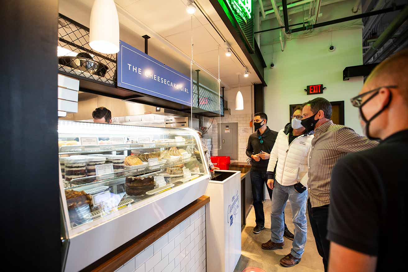 People reviewing menu at cheesecake bakery counter.