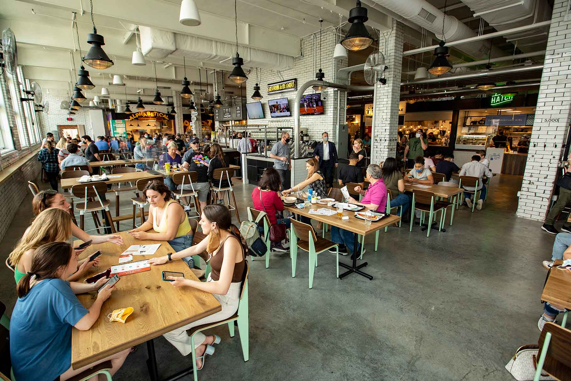 Diners seated at wooden tables inside open air food hall.