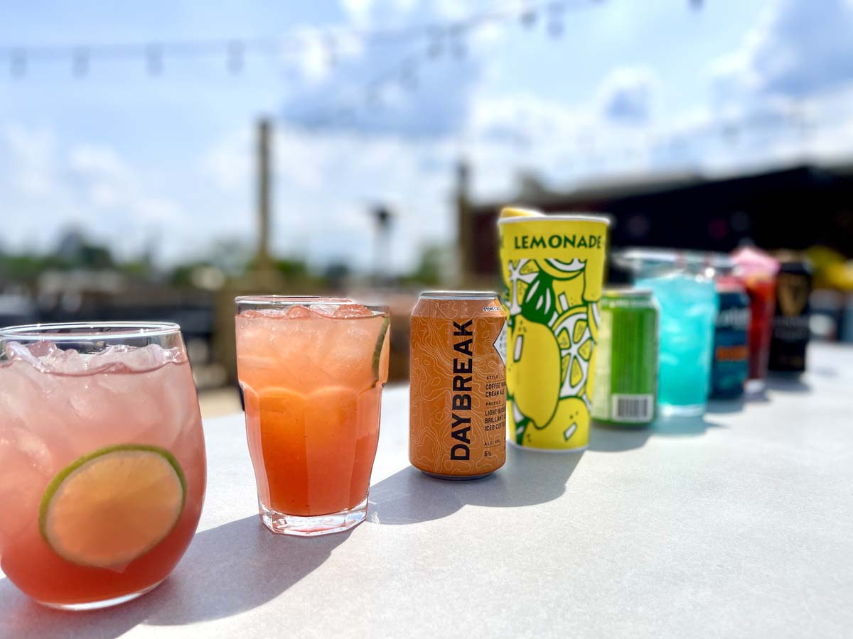 Cocktails of various colors, shapes and sizes lined up on outdoor patio table.