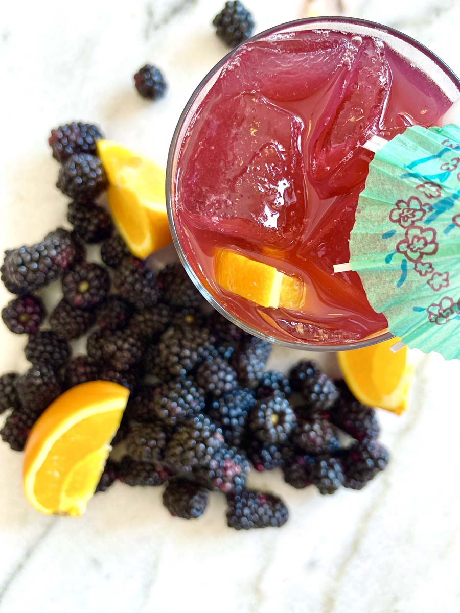 Top view of red beverage in glass with umbrella decoration surrounded by blackberries and orange slices.