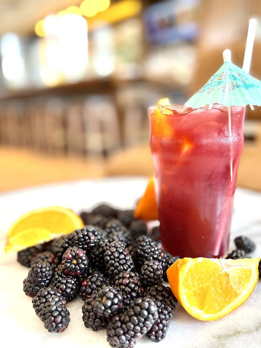 Red beverage in glass with umbrella decoration surrounded by blackberries and orange slices.