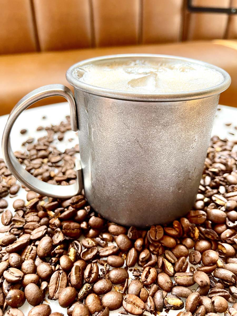Frosty beverage in a metal cup sitting on coffee beans.