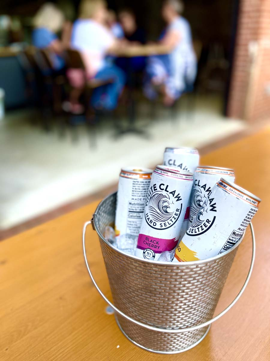 Silver bucket of ice filled with White Claw canned beverages.