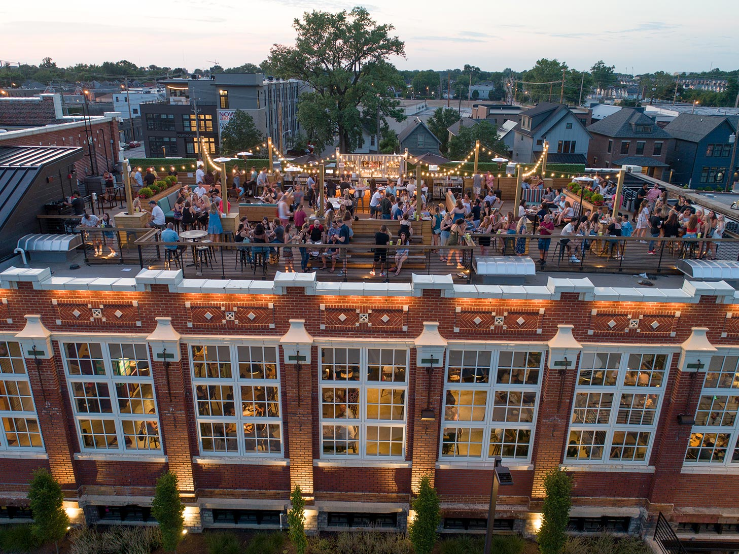 Aerial view of Budd Dairy Food Hall rooftop with lots of people at dusk.