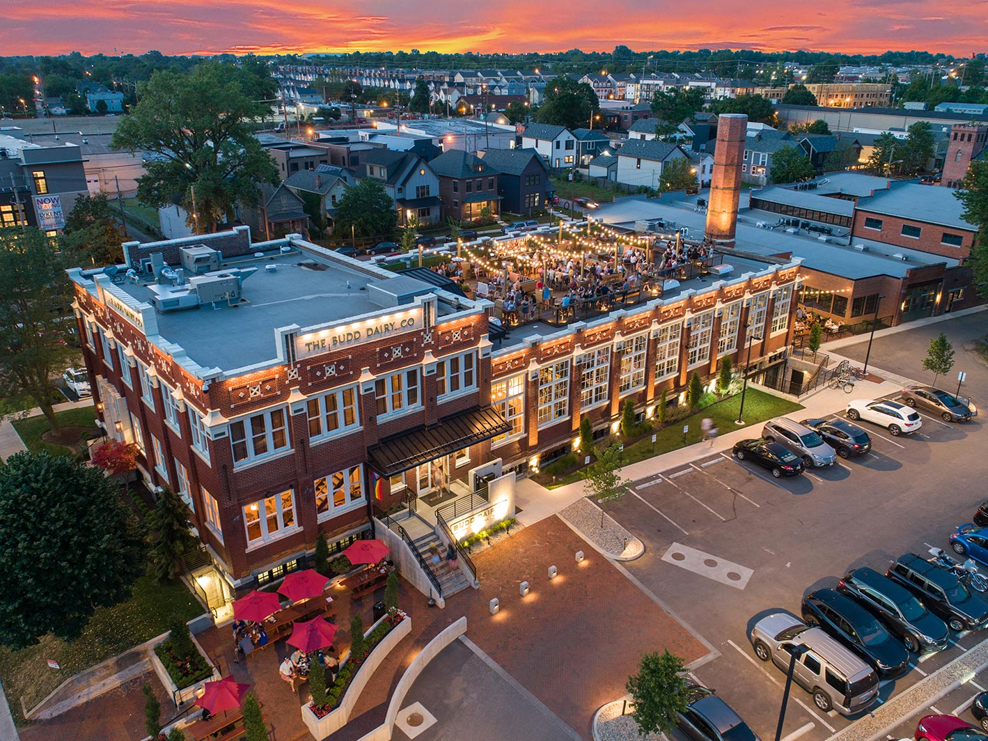 Aerial view of Budd Dairy Food Hall at sunset showing lighted exterior and people on rooftop.