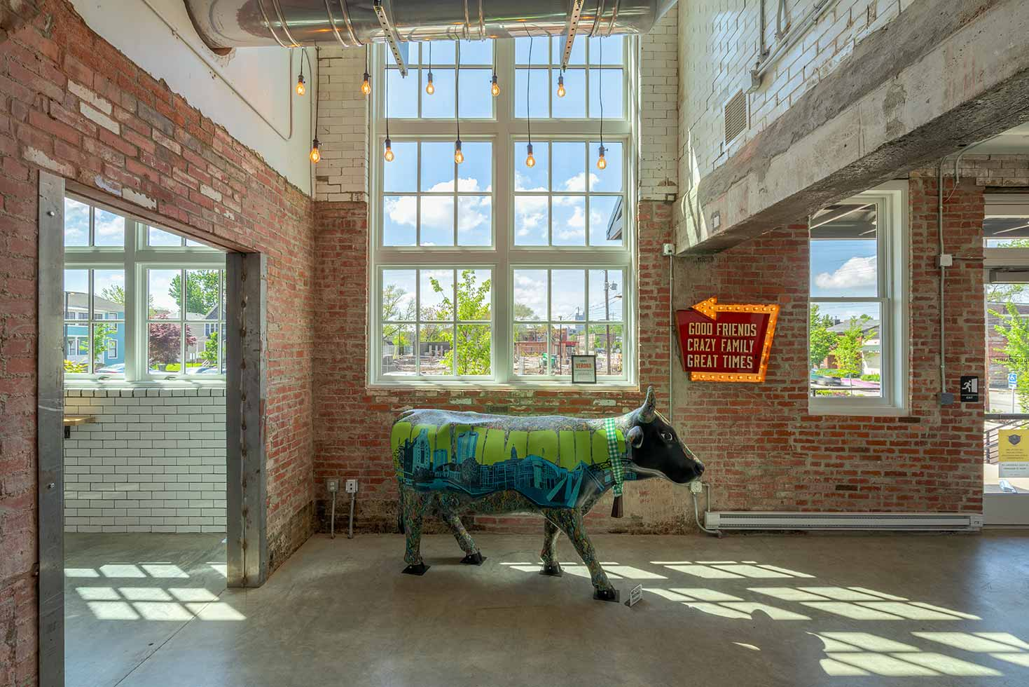 The Budd Dairy Food Hall mascot cow at the front entrance in front of large windows.