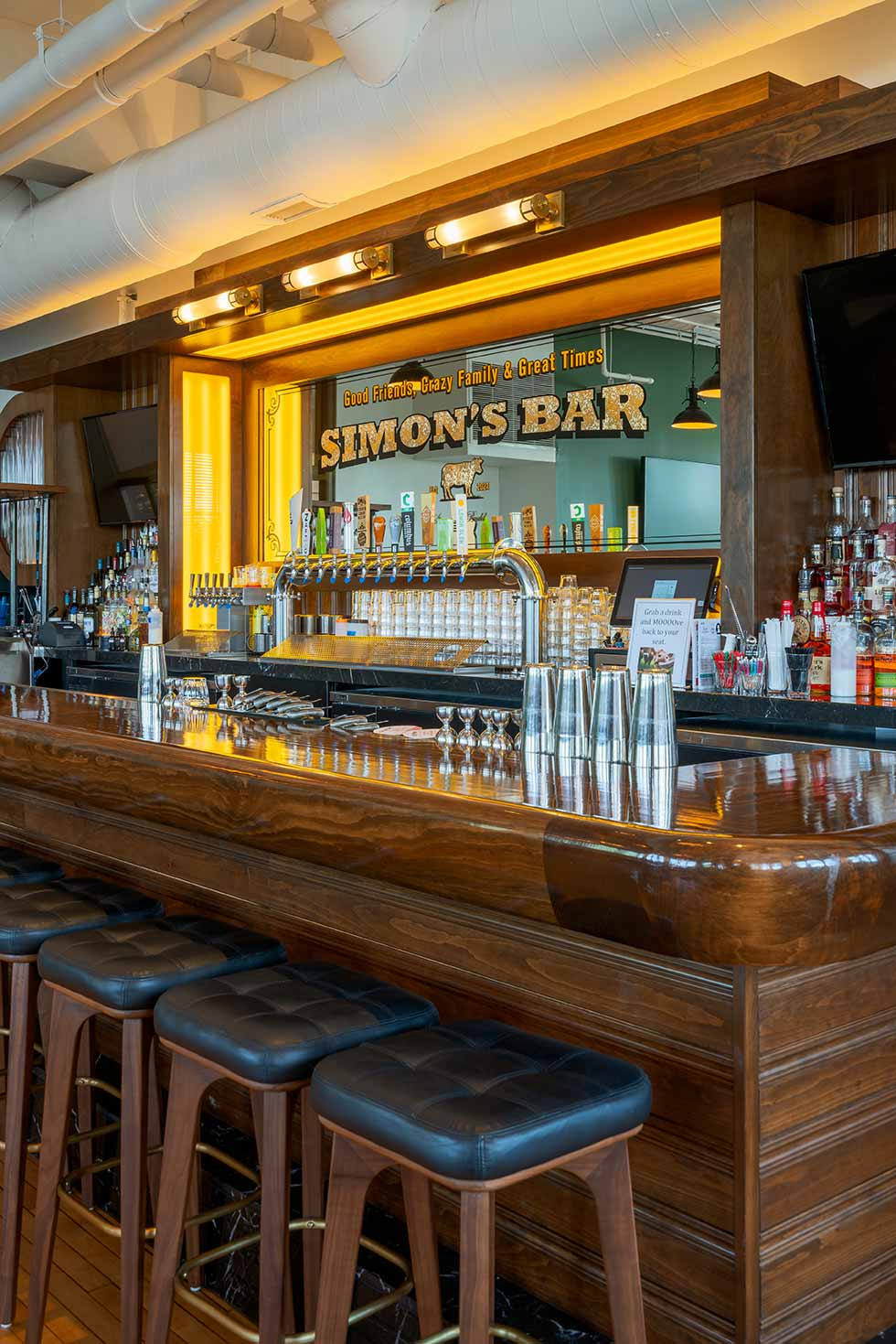 Simon's Bar with long wooden bar and stools.
