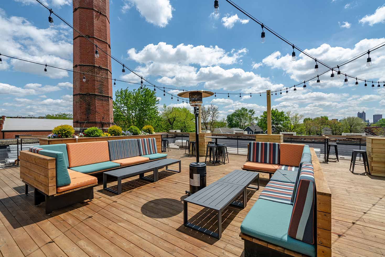 Rooftop at Budd Dairy Food Hall with long couch seating and wood deck.