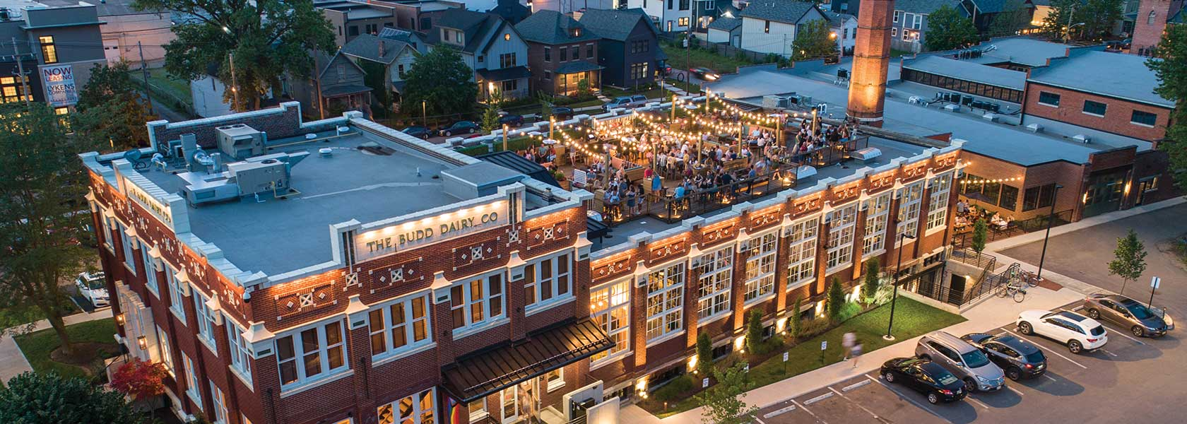 Aerial view of Budd Dairy Food Hall at sunset with crowd on roof.