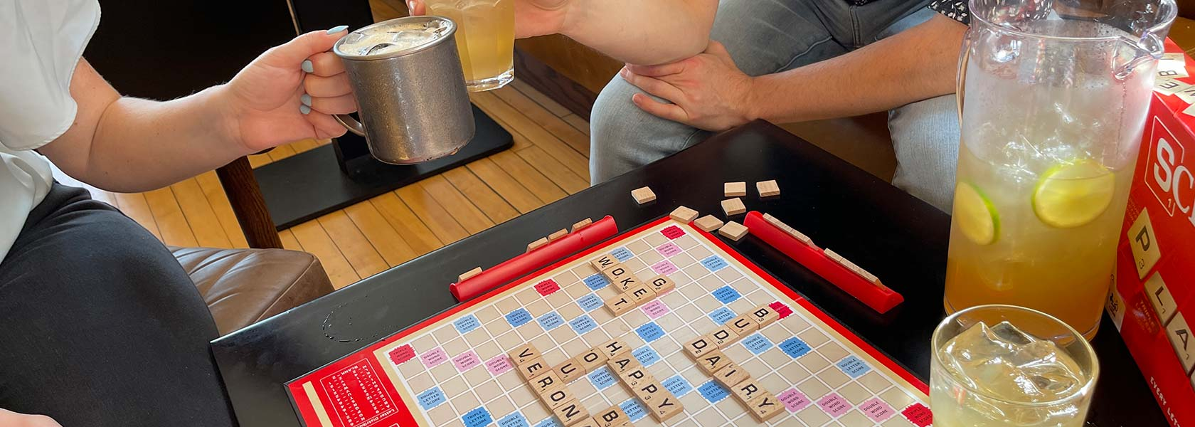 Hands toasting with cocktails above Scrabble game board in play.
