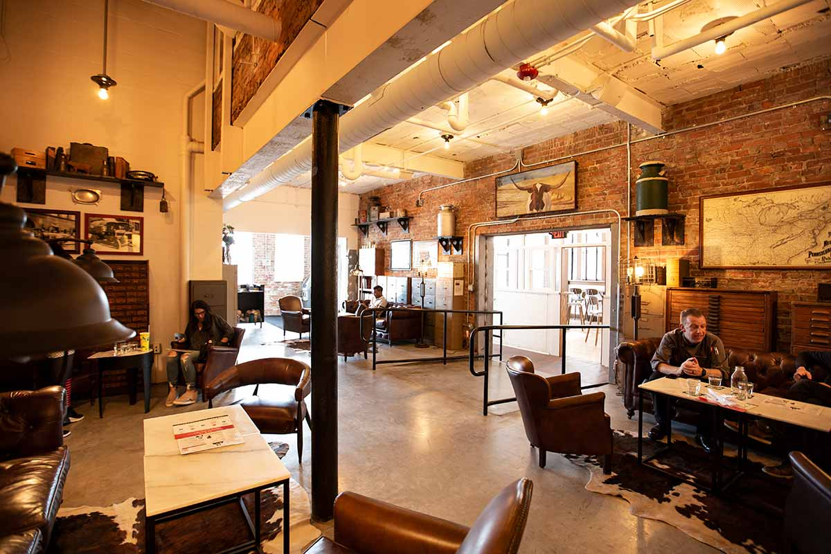 Cozy lounge area with leather seating and low-lights, brick walls.