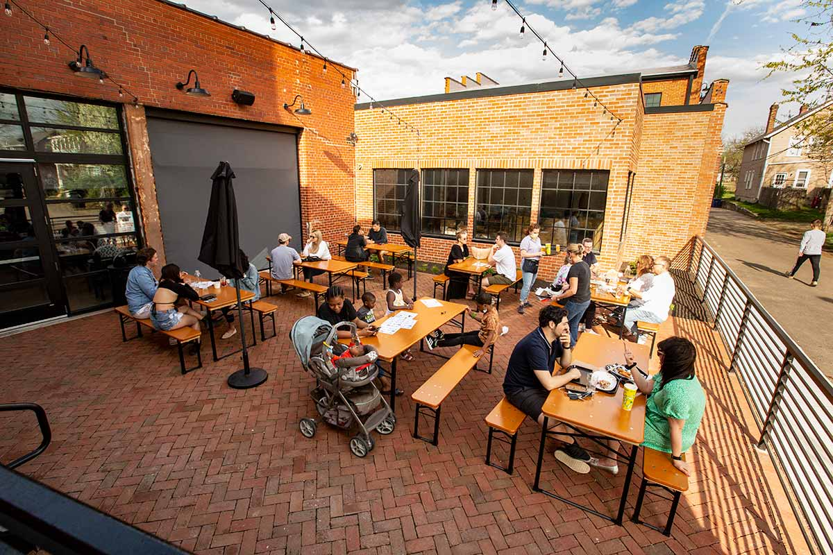 Outdoor patio area with long tables and people enjoying warm weather.