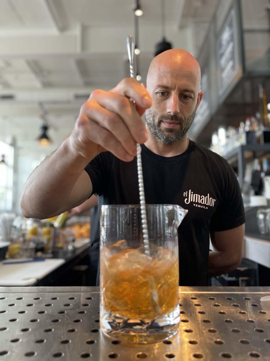 Bar chef stirring pitcher beverage with long glass stirrer