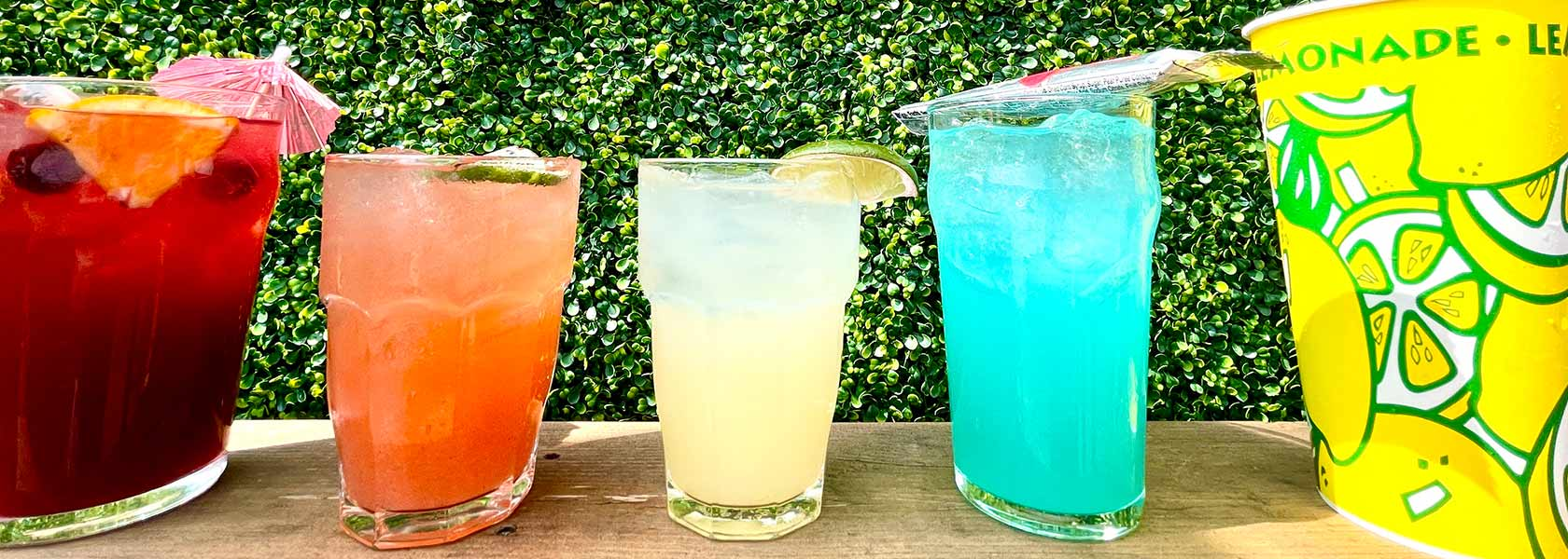 Colorful cocktails in a row with hedge background