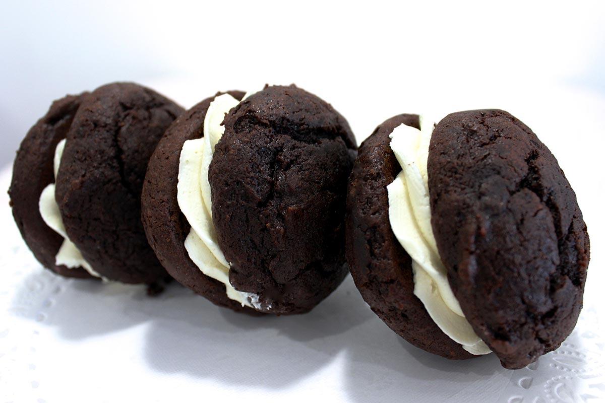 Three vanilla cream filled chocolate whoopee cake cookies.