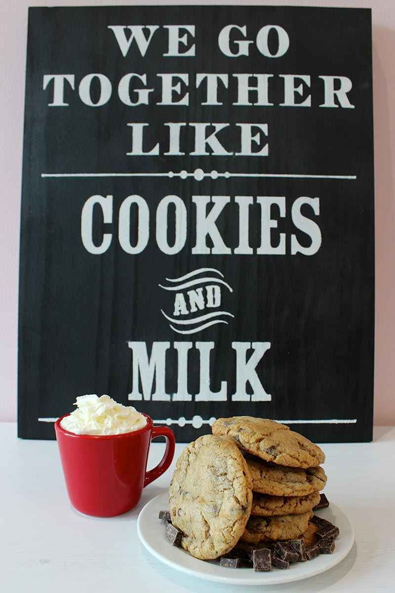 Chalkboard sign reading We Go Together Like Cookies and Milk behind mug and stack of chocolate chip cookies.