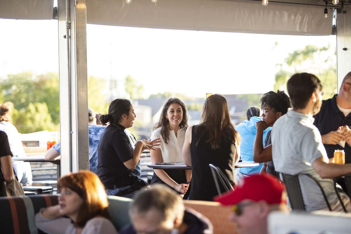 Group of women seated and socializing in an outdoor bar setting