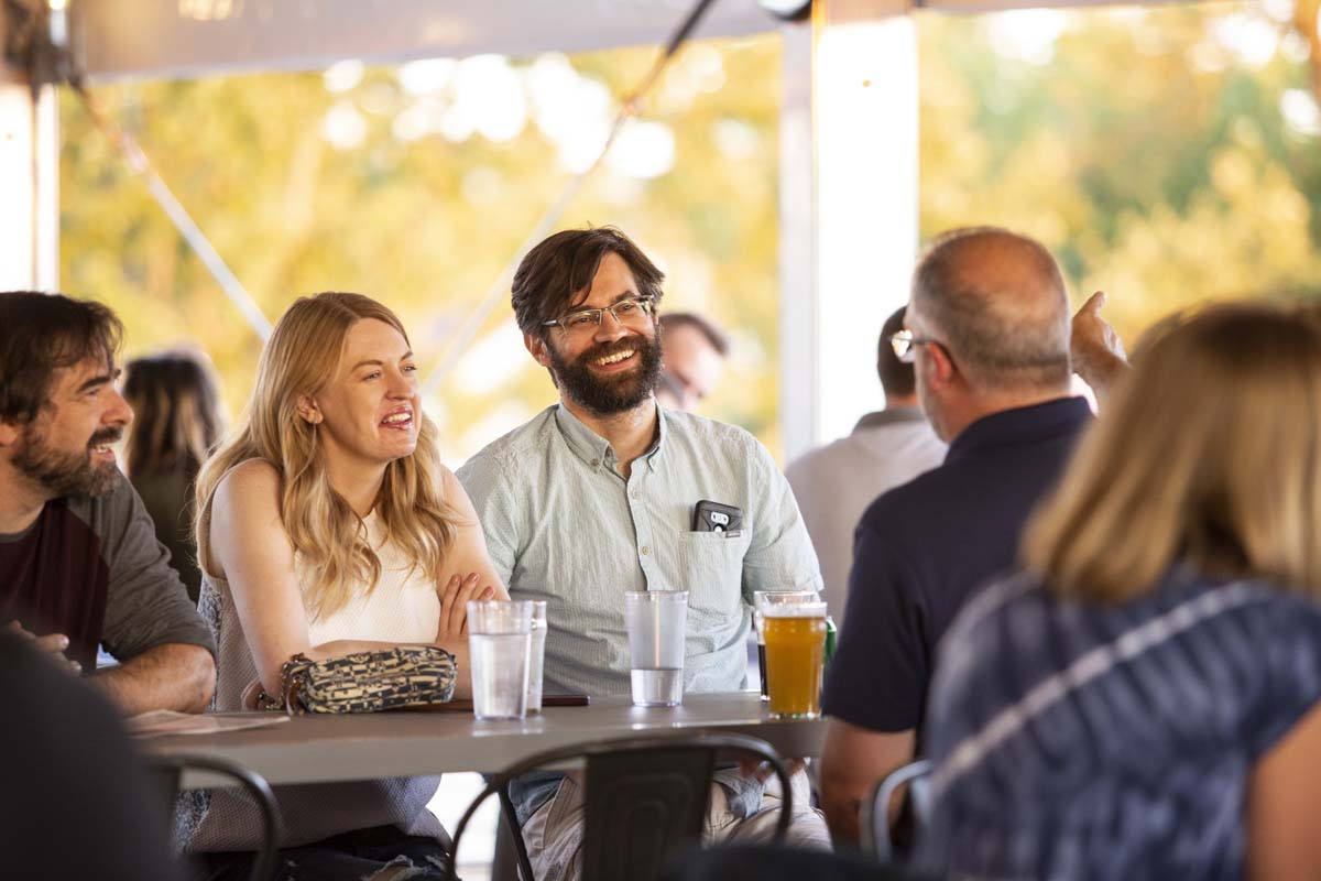 Group of friends socializing in outdoor bar setting