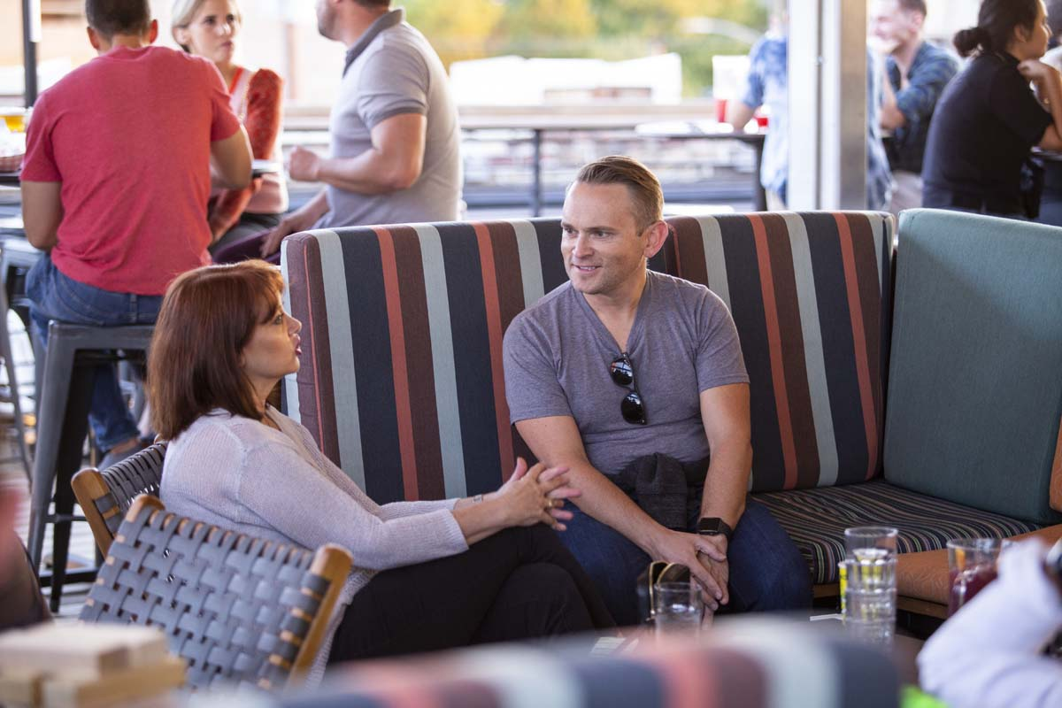 Man and woman talking in outdoor bar seating area