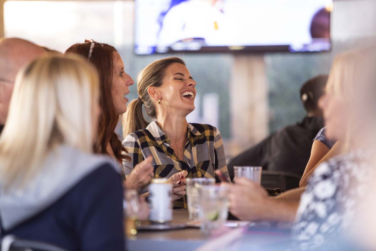 Woman laughing with friends in an outdoor bar setting