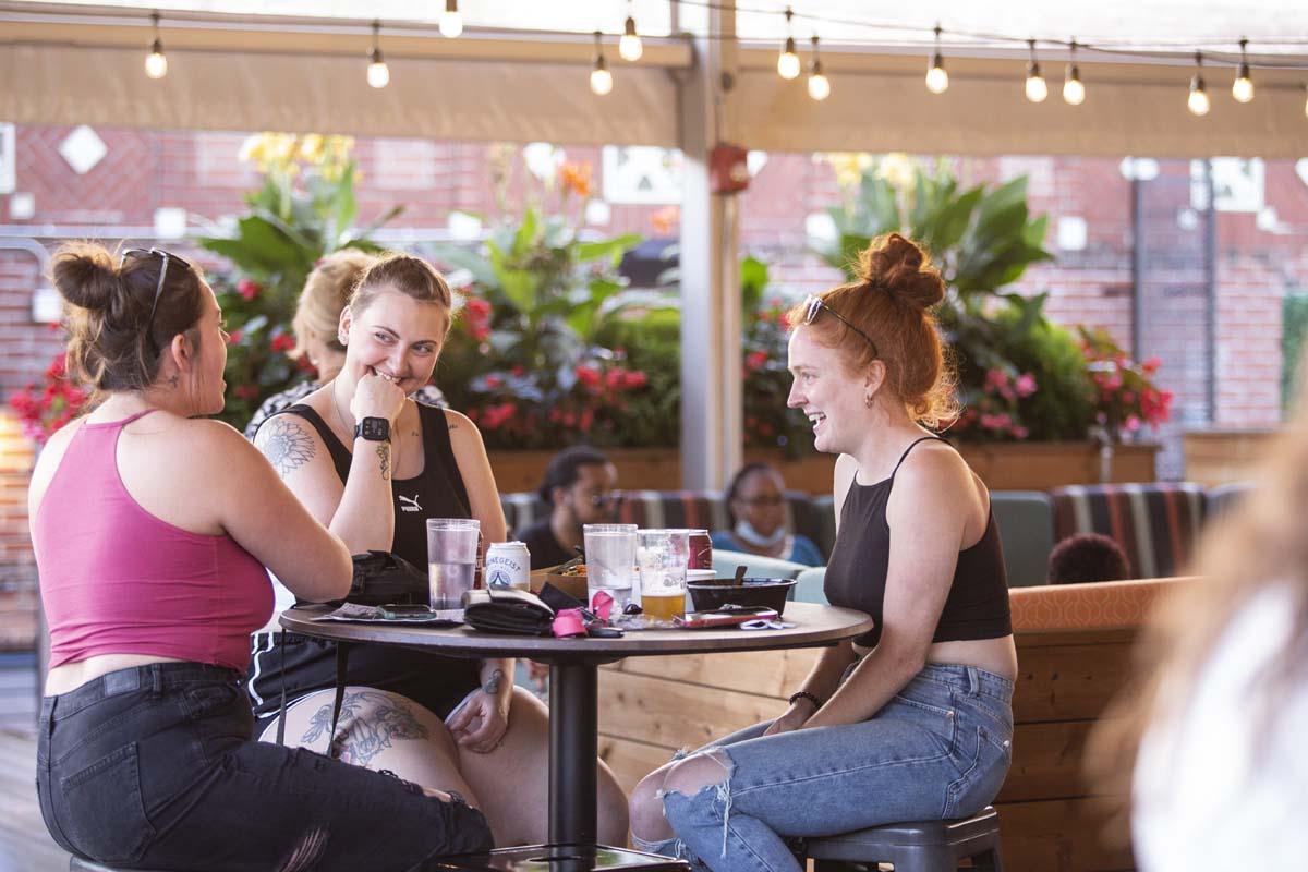 Two women socializing in an outdoor bar setting