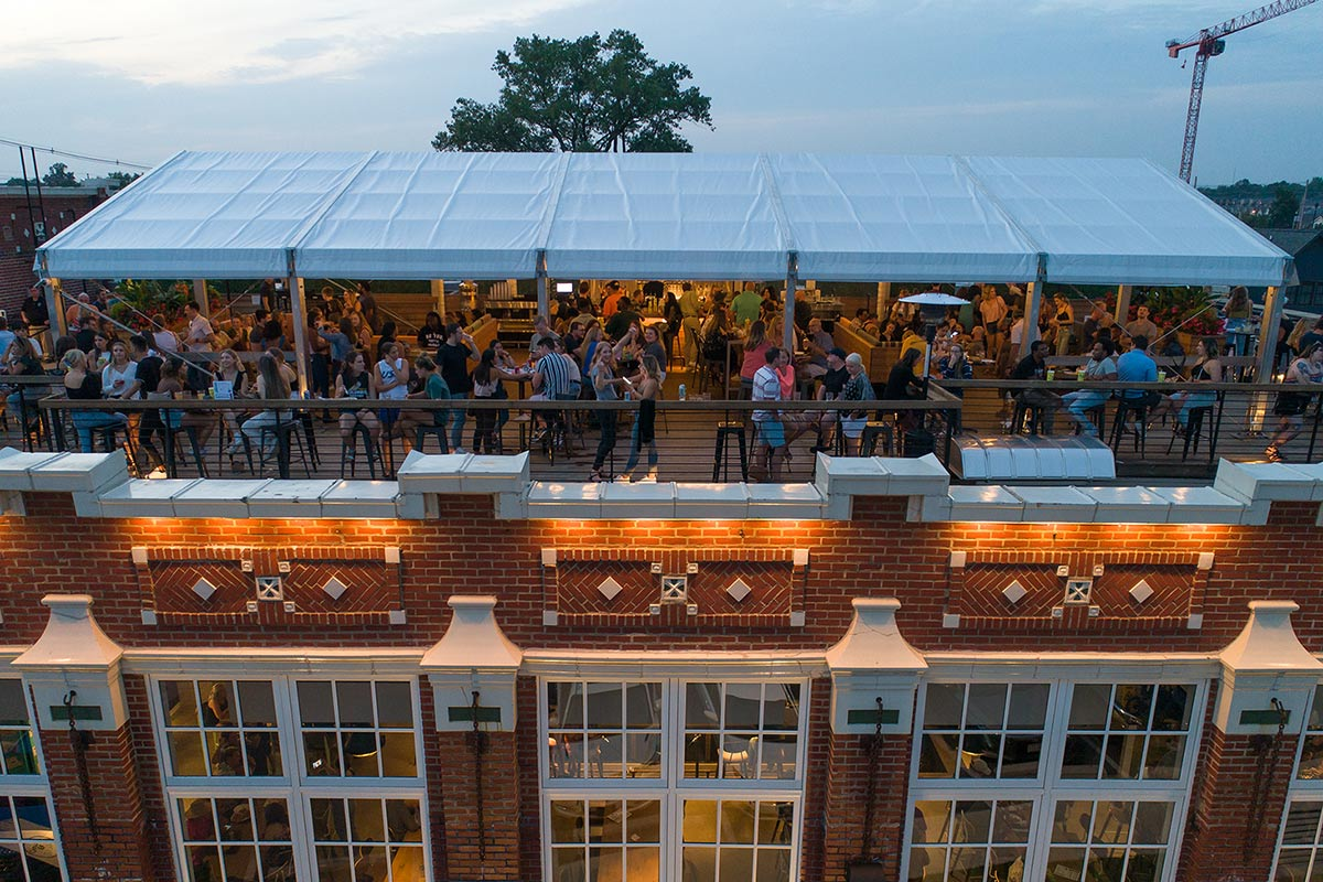 Drone view of crowd under white canopy on the rooftop at Budd Dairy Food Hall in Columbus, Ohio.