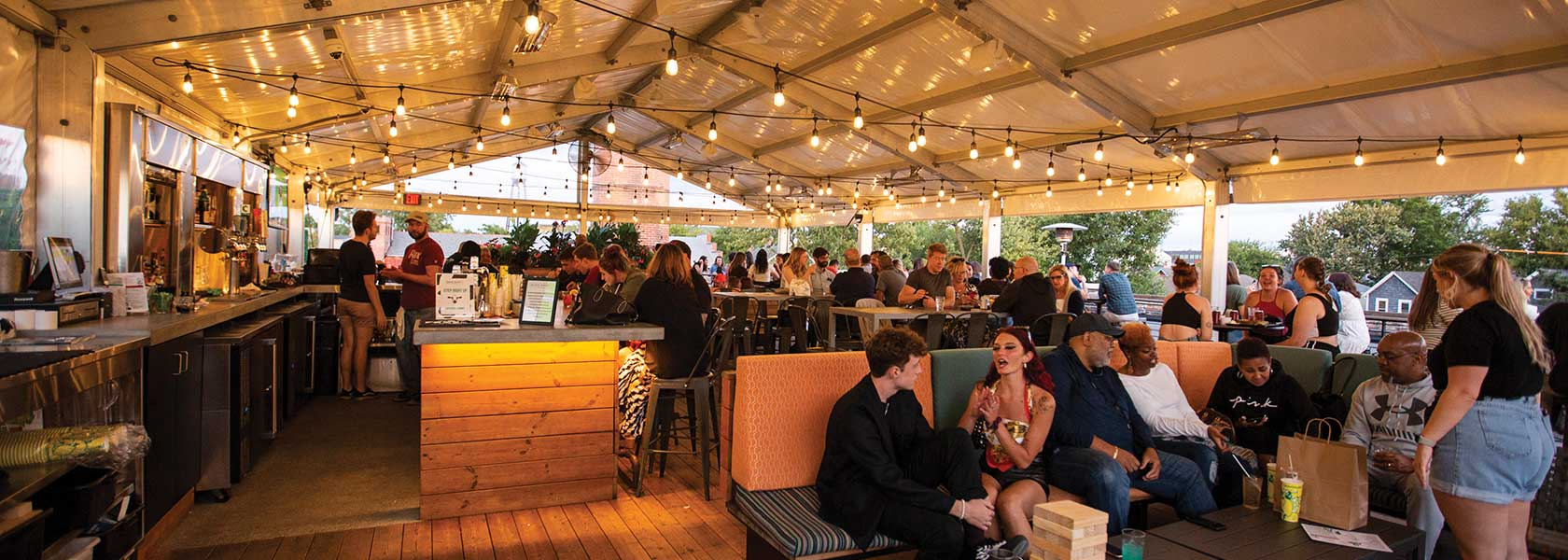 Guests socializing under a white, lighted canopy on the Budd Dairy Food Hall rooftop